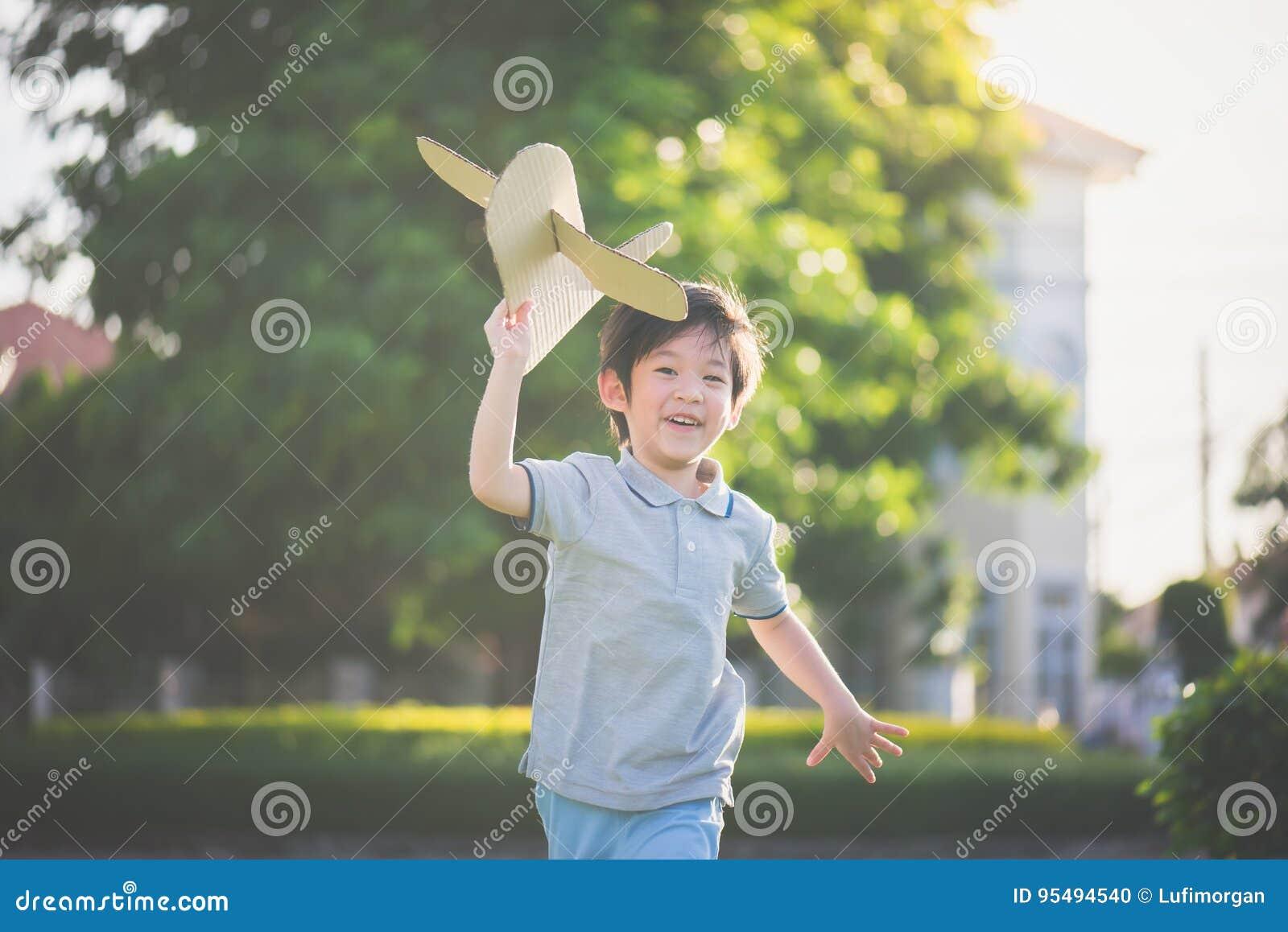 Asiatiskt barn som spelar pappflygplanet