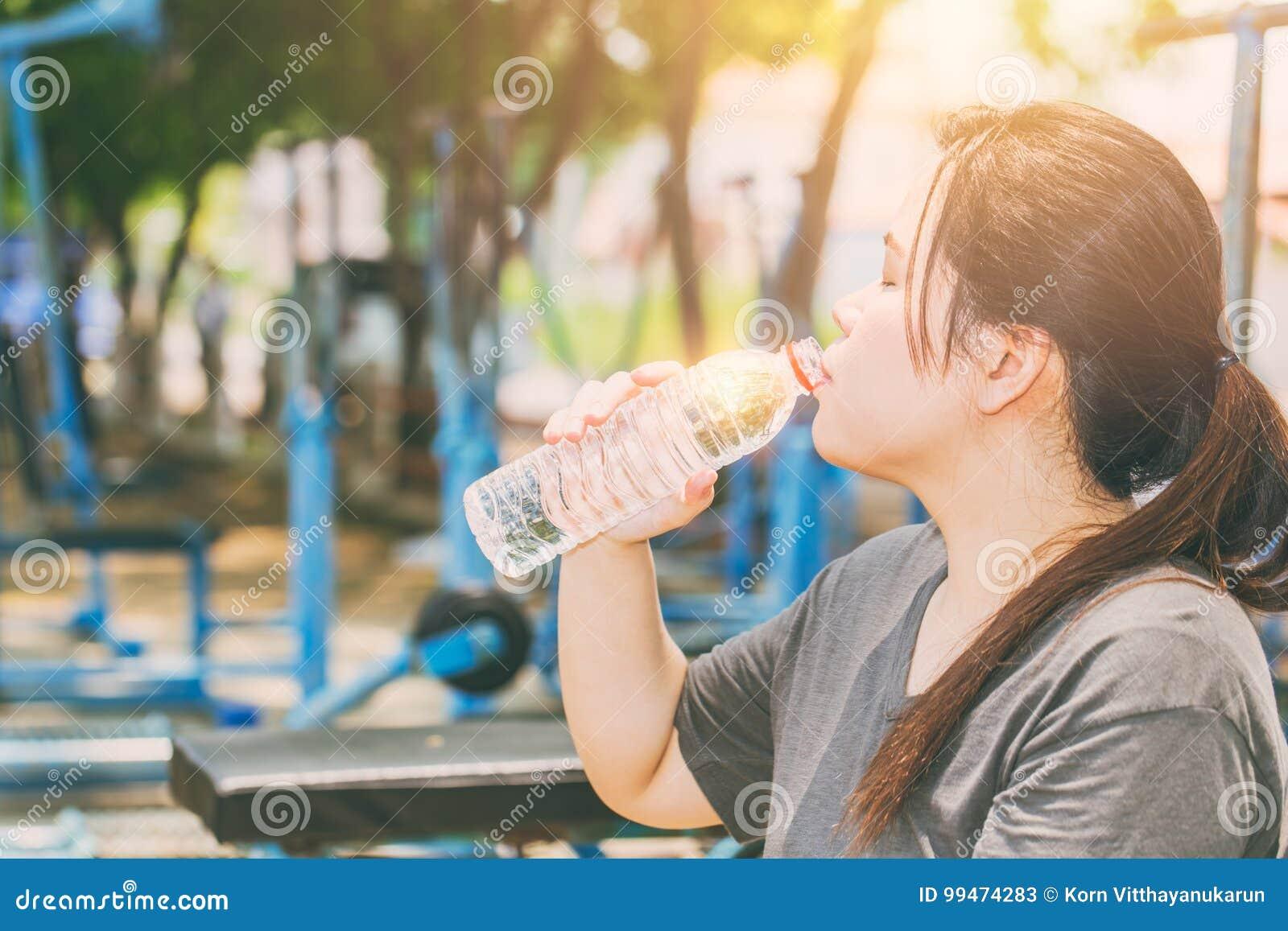 Asiatiskt kvinnadricksvatten i varm dag