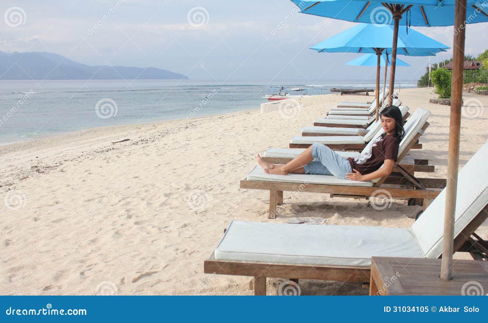 Asiatiskt kvinnasammanträde på solstol på den tropiska stranden