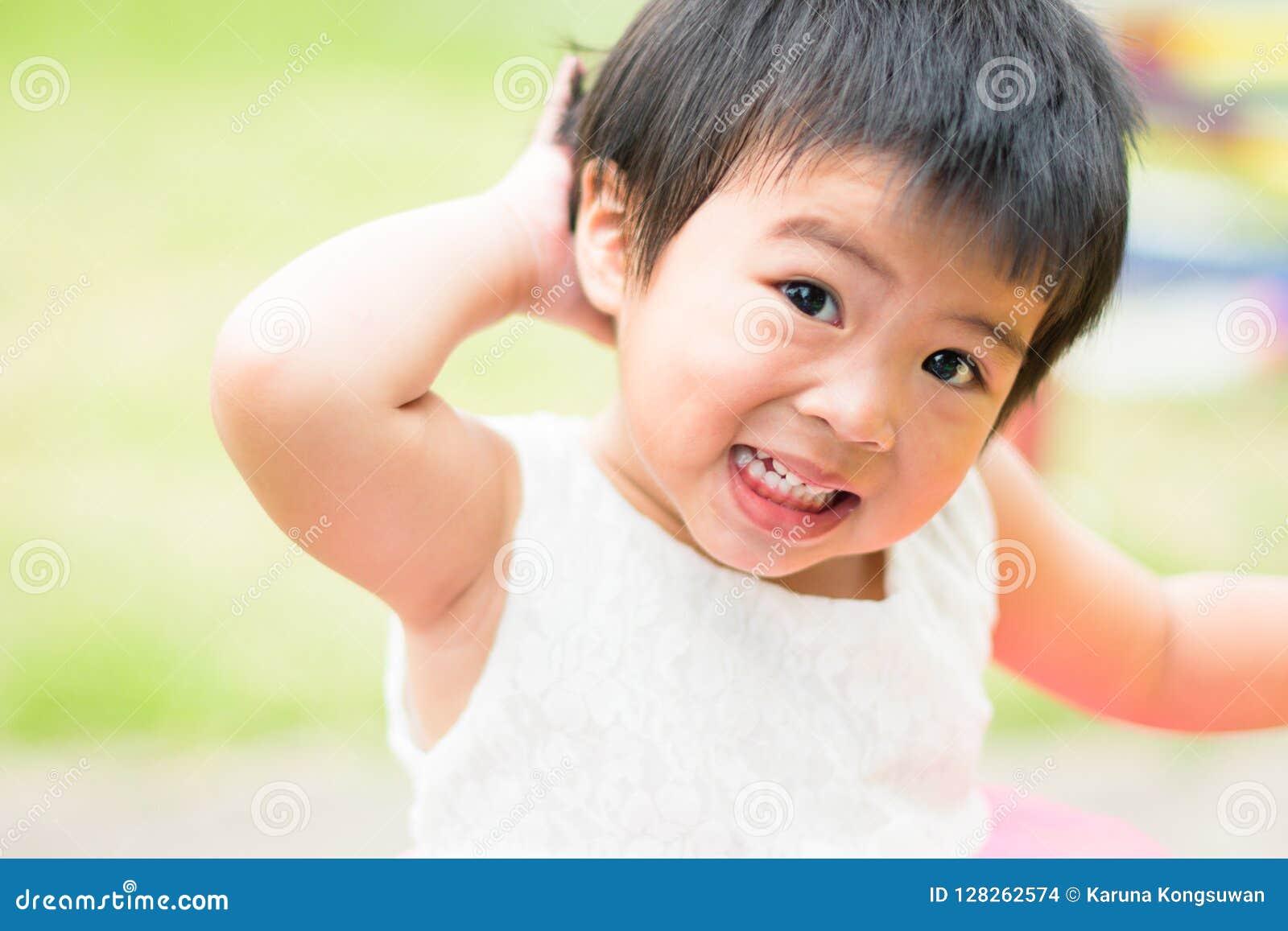 Asiatiskt litet barn som skriker i lekplatsbakgrund