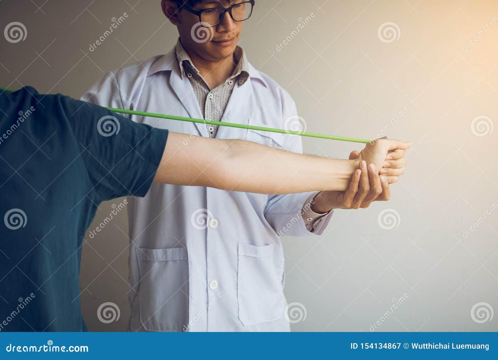 Asiatiskt manligt nedstigningsarbete f?r fysisk terapeut och hj?lpa att skydda h?nderna av patienter med patienten som g?r str?ck