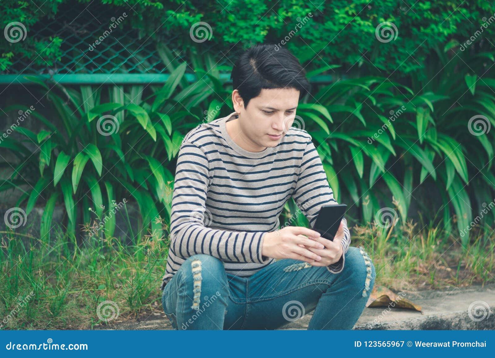 Asiatiskt mansammanträde och användasmartphone