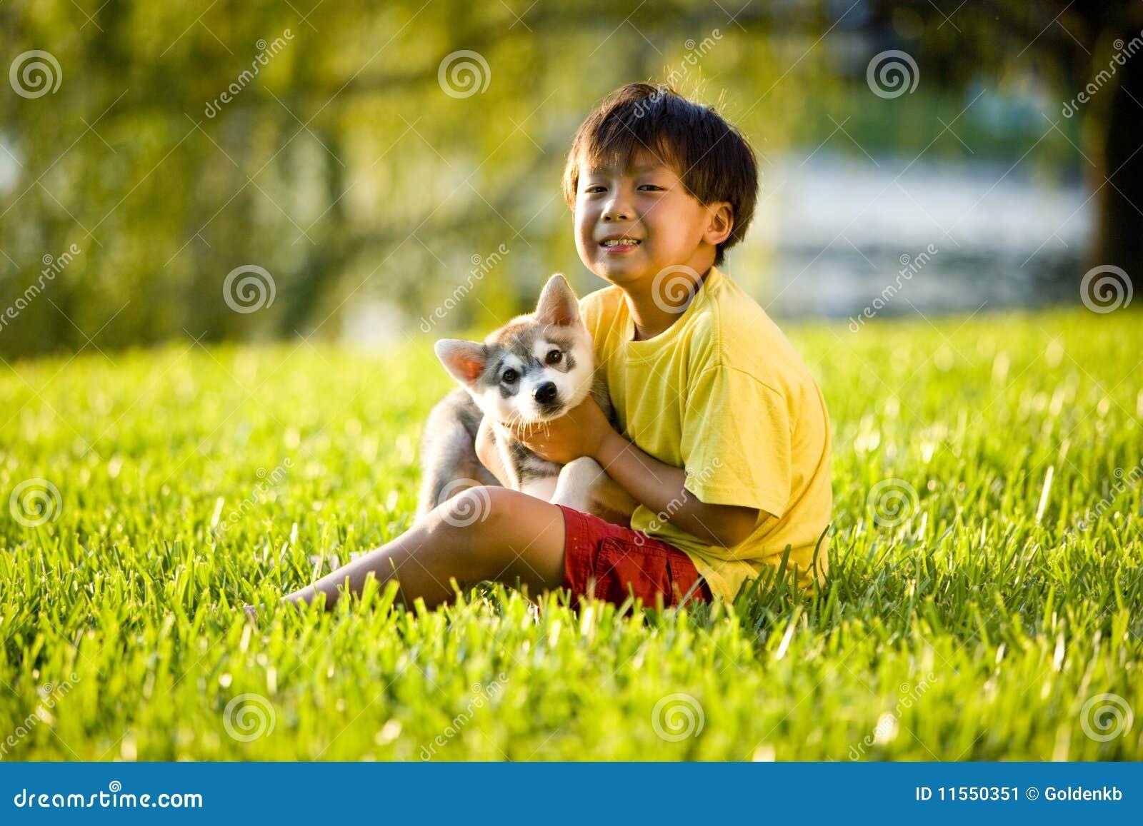 Asiatiskt pojkegräs som kramar sittande barn för valp