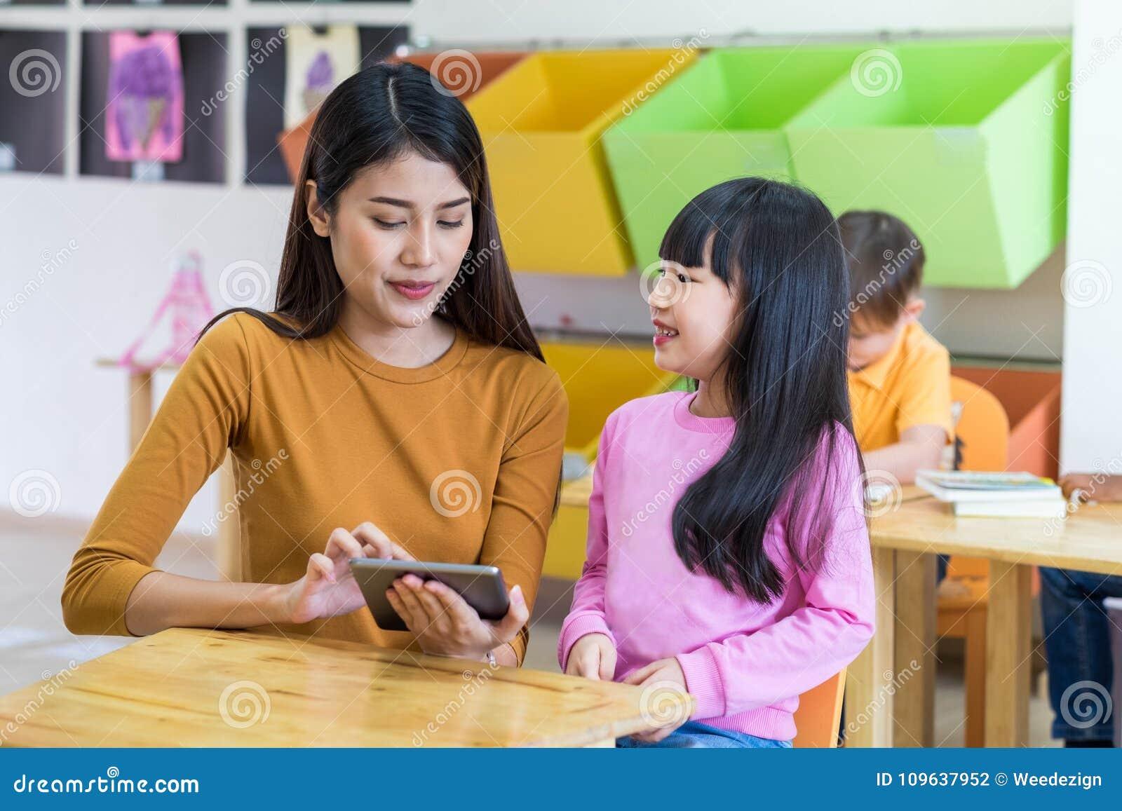 Asien-Lehrerin unterrichten Studentin mit Tablet-Computer im Cl