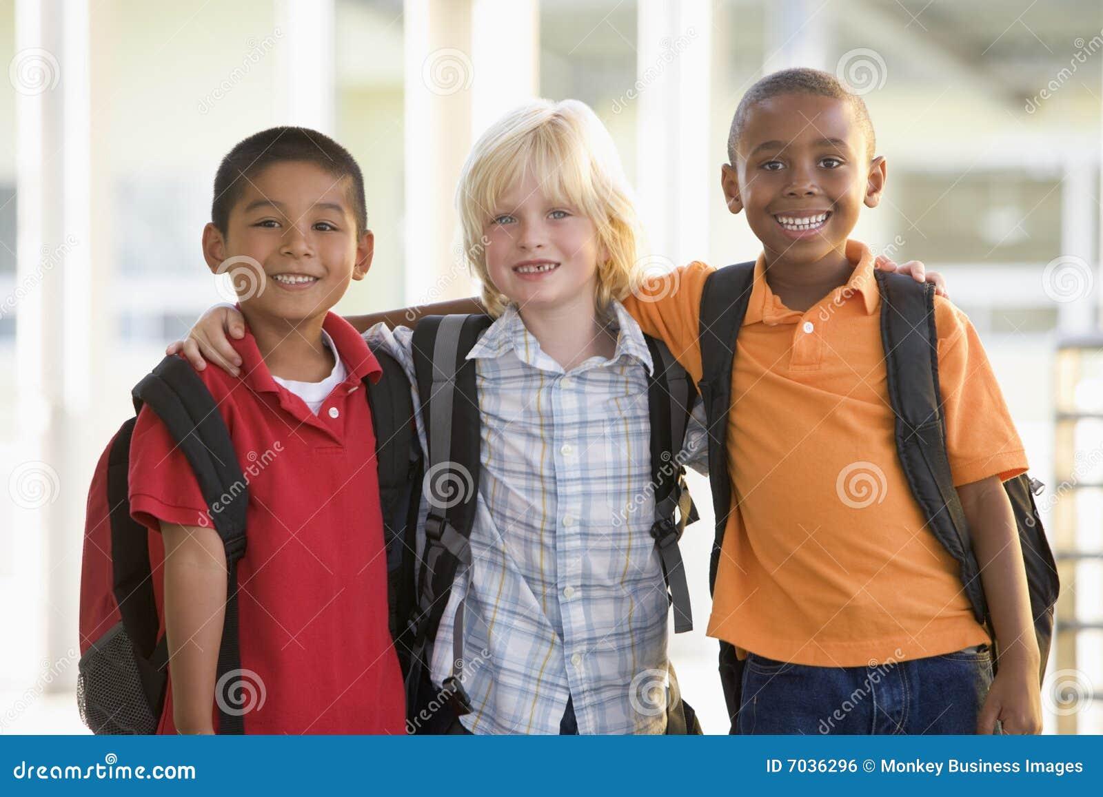 Asilo dei ragazzi che si leva in piedi insieme tre