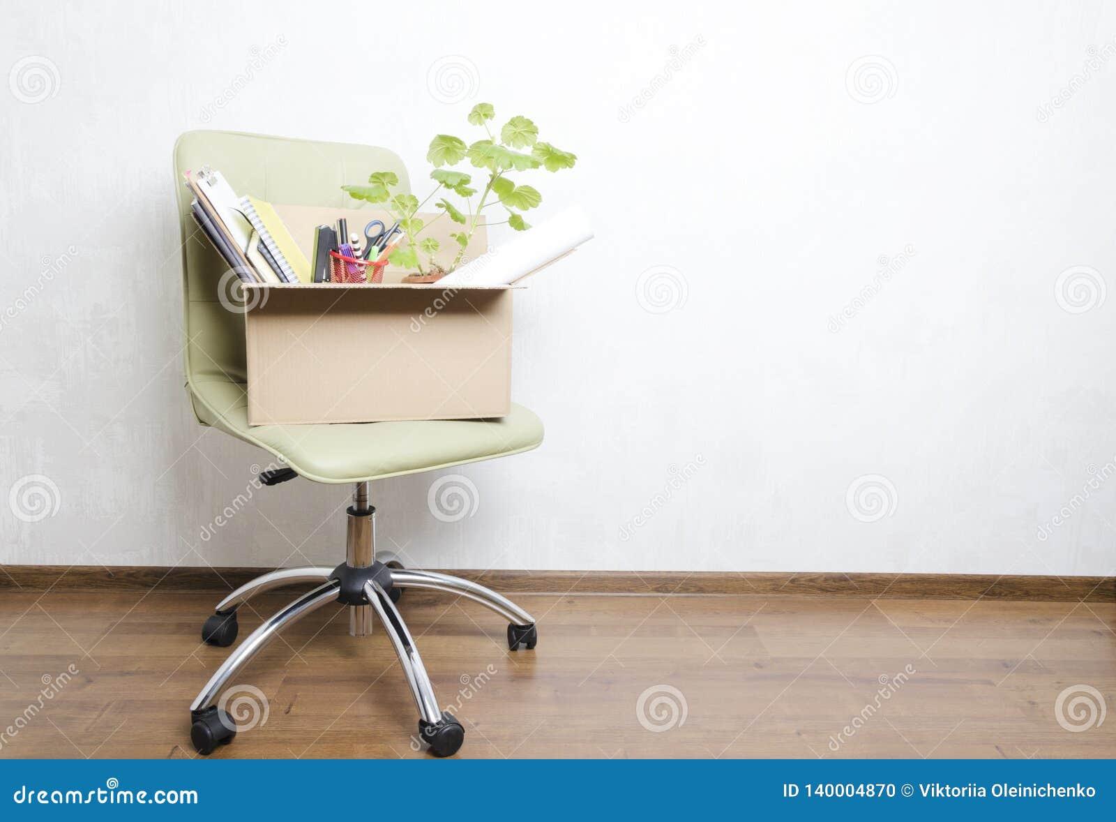Ask med personliga objekt som står på stolen i kontoret Begrepp av att flytta sig eller avskedandet