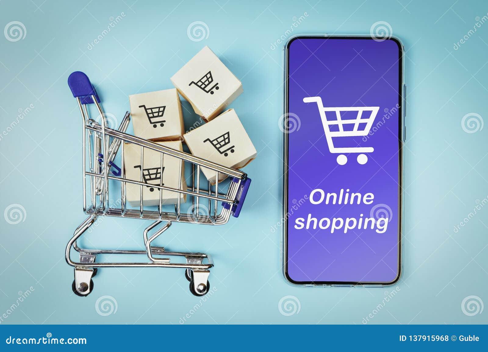 Askar i en shoppa vagn och en smartphone på blå bakgrund Begrepp: online-shopping, e-kommers och leverans av gods