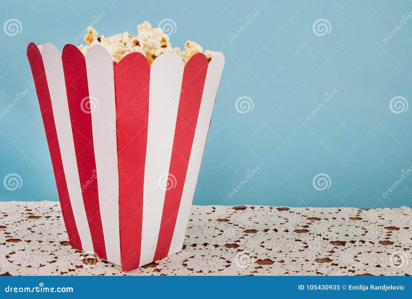 Asken av popcorn på blå bakgrund och snör åt doilyen med utrymme för text