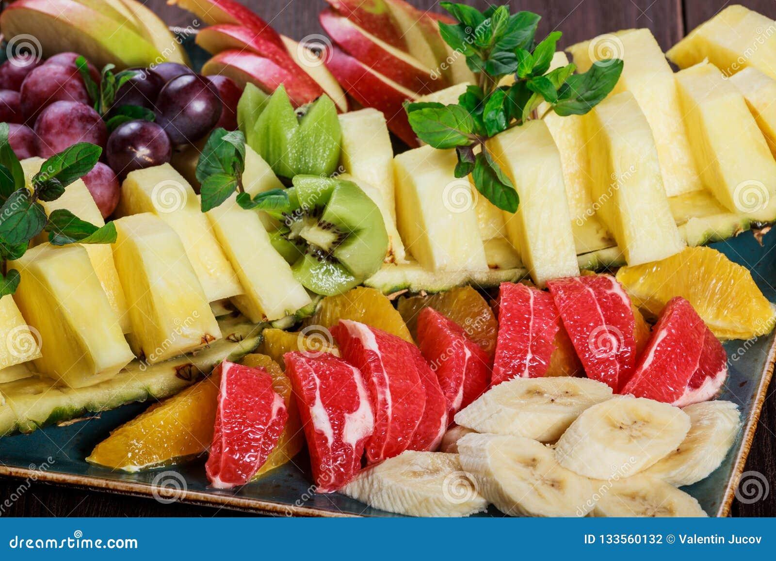 Asortowane świeże owoc na talerzu Apple, winogrona, kiwi, ananas, grapefruitowy, pomarańczowy, banan i mennica na drewnianym stol