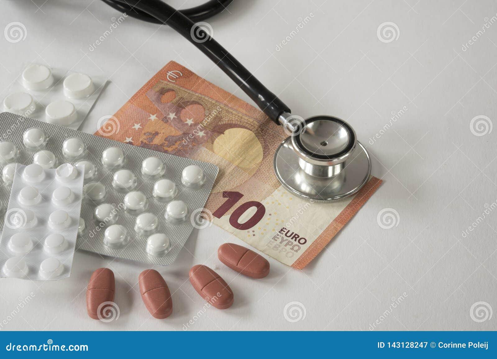 Asortowane farmaceutyczne medycyn pigułki, pastylki, stetoskop i pieniądze przeciw białemu tłu,
