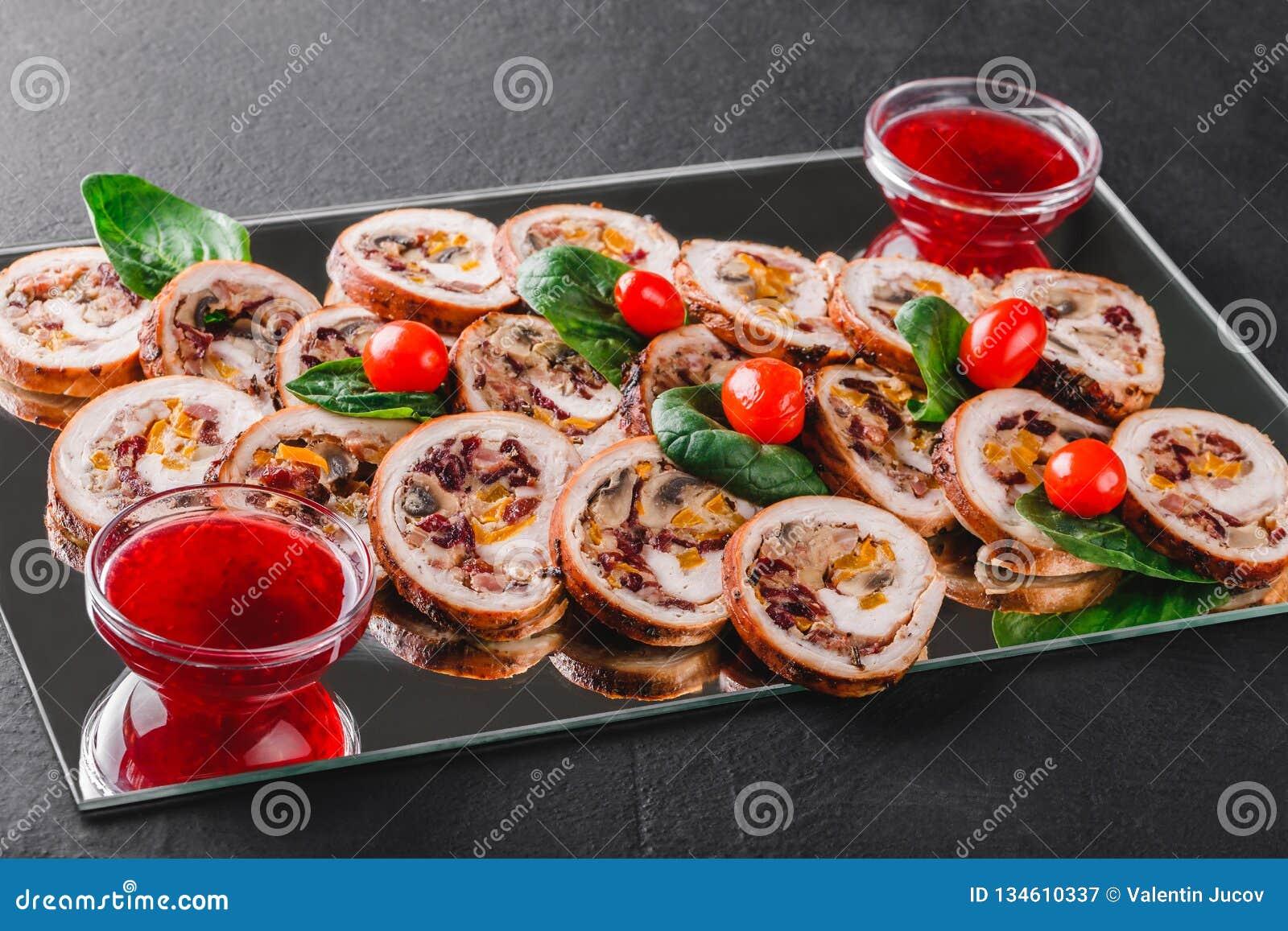 Asortowany mięso, faszerować kurczak rolki, mięsne rolki faszerował z pieczarkami i suszył morele na czarnego iłołupka tle, cranb