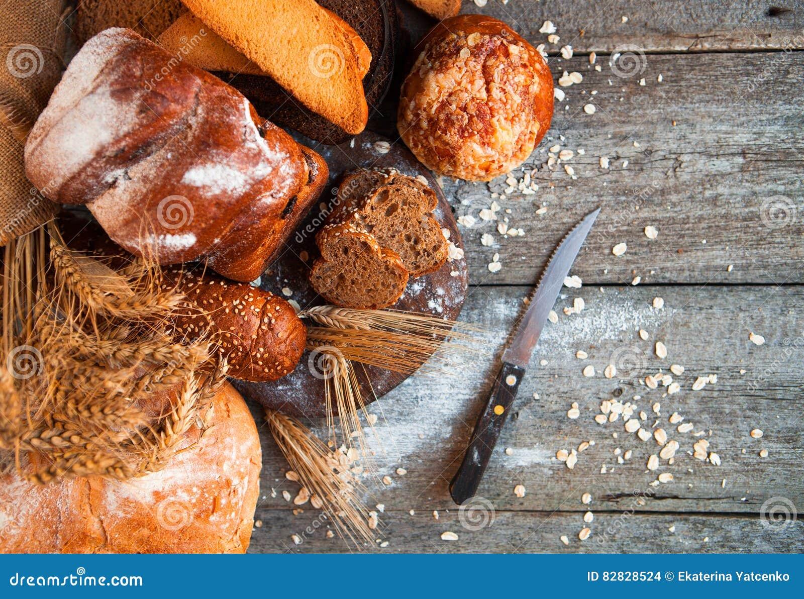 Asortyment świeży piec chleb na drewnianym stołowym tle