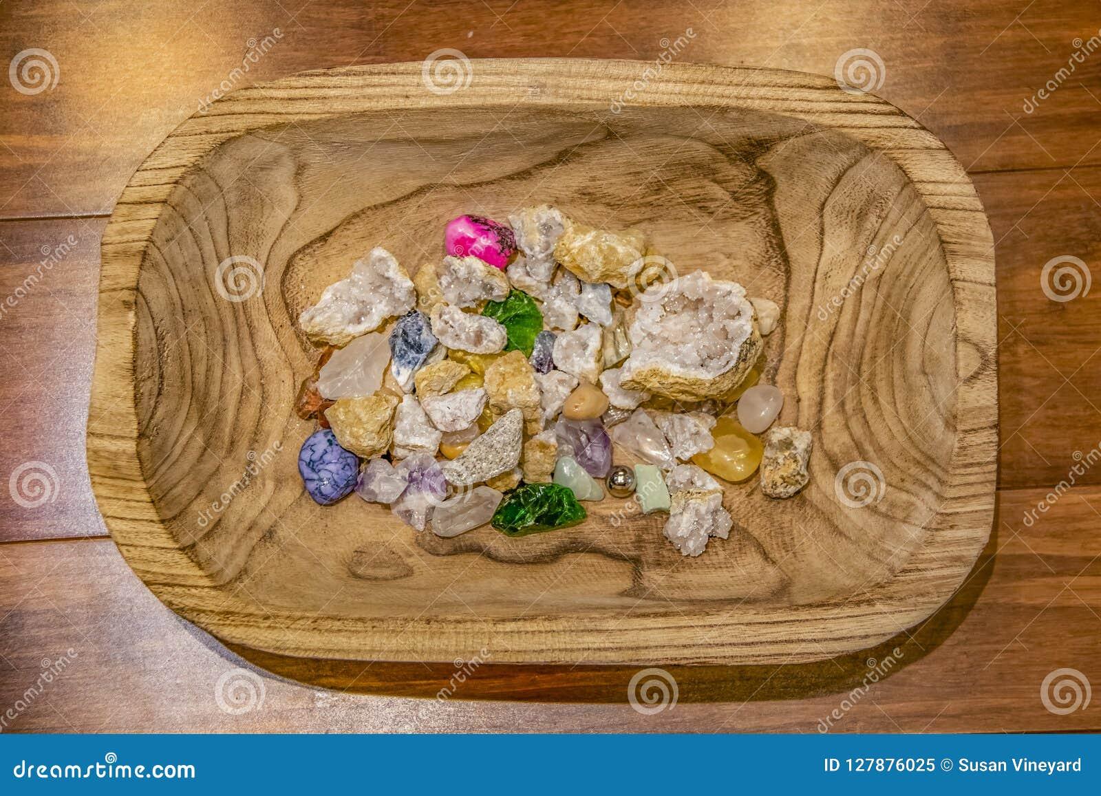 Asortyment kryształy i kamienie różni kolory i tekstury w rzeźbiącym drewnianym pucharu obsiadaniu na drewnianej deski powierzchn