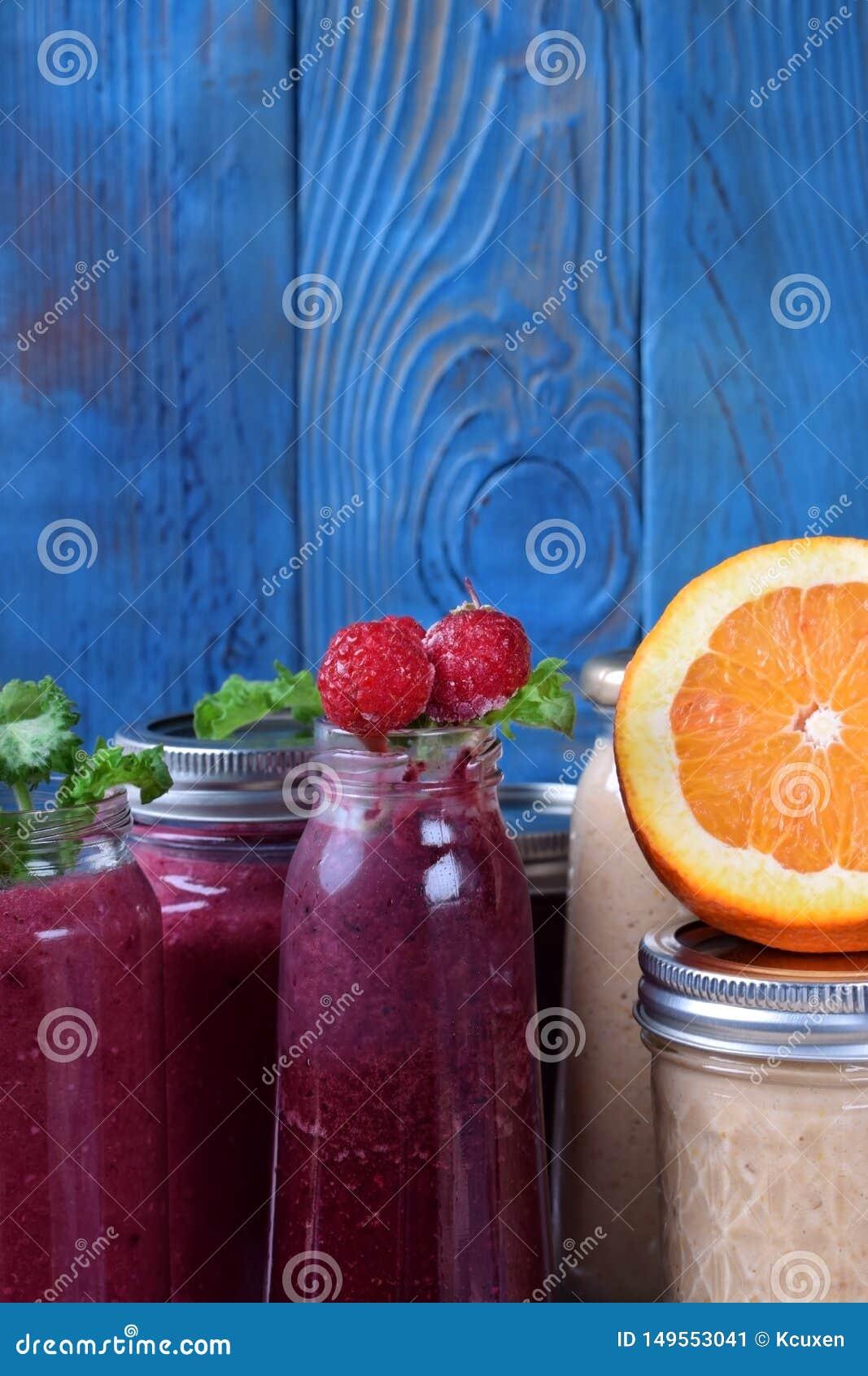 Asortyment różni smoothies nakrywający z owoc, jagodami i mennicą na stole,