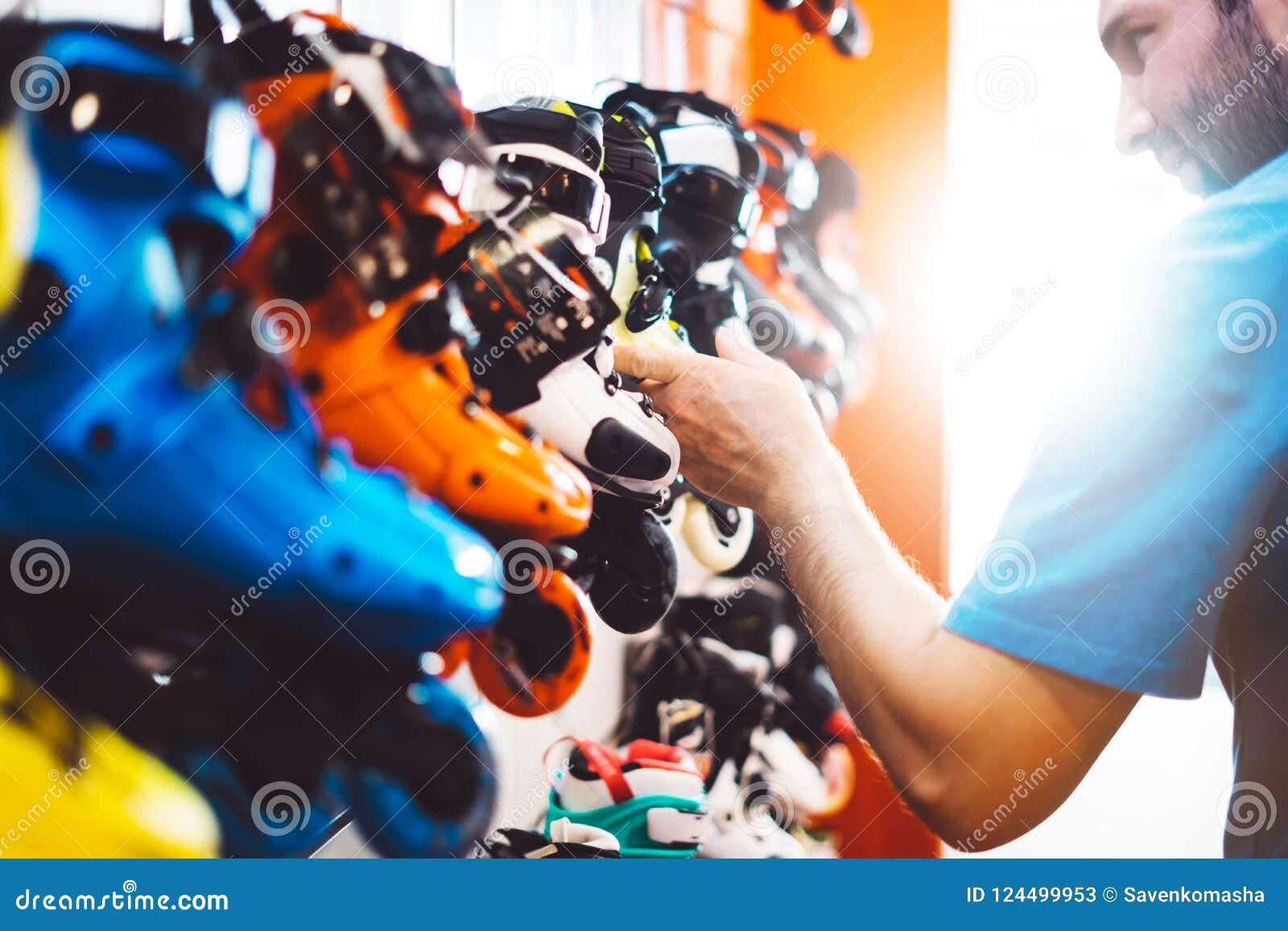 Asortyment rolkowe łyżwy odizolowywać w sklepu sklepie, osoby wybierać i zakupu koloru wrotkach na backgraund słońcu, migoczą, zd