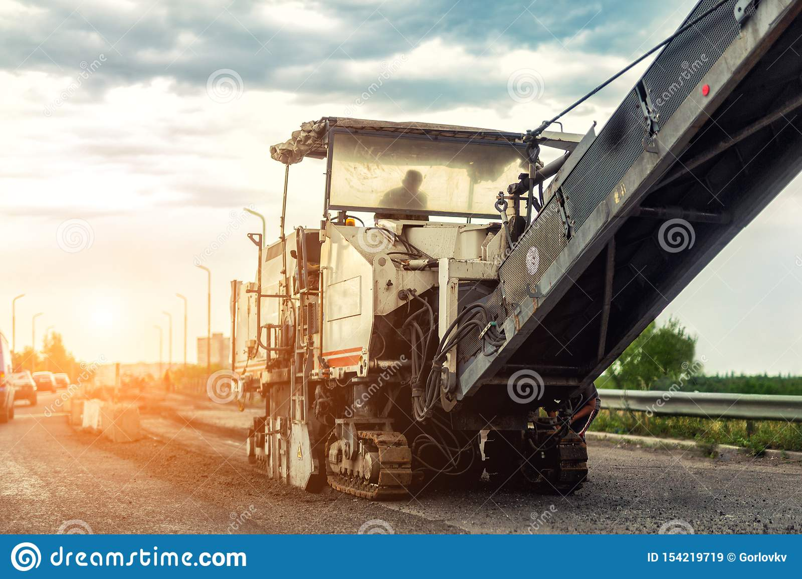 Asphalt milling and grinding machine at road repair and construction site. Highway renewal with heavy machinery