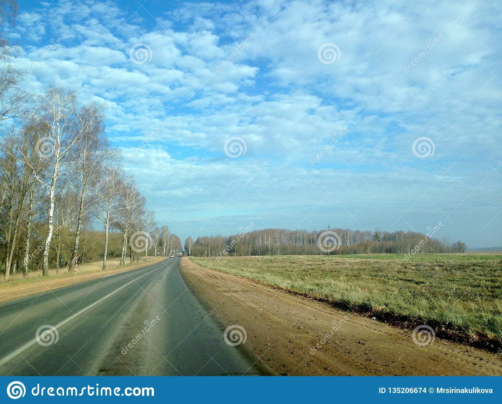 Asphalt road in retro style through the fields and forests against the blue sky with lush clouds