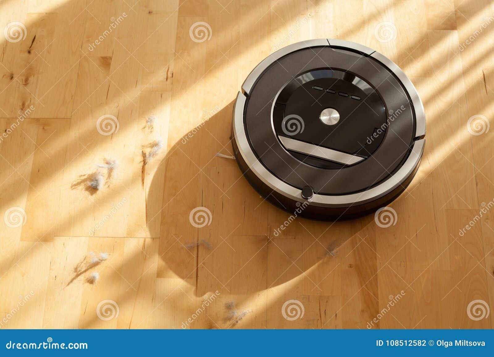 Aspirador robótico en la limpieza elegante del piso de madera laminado técnica