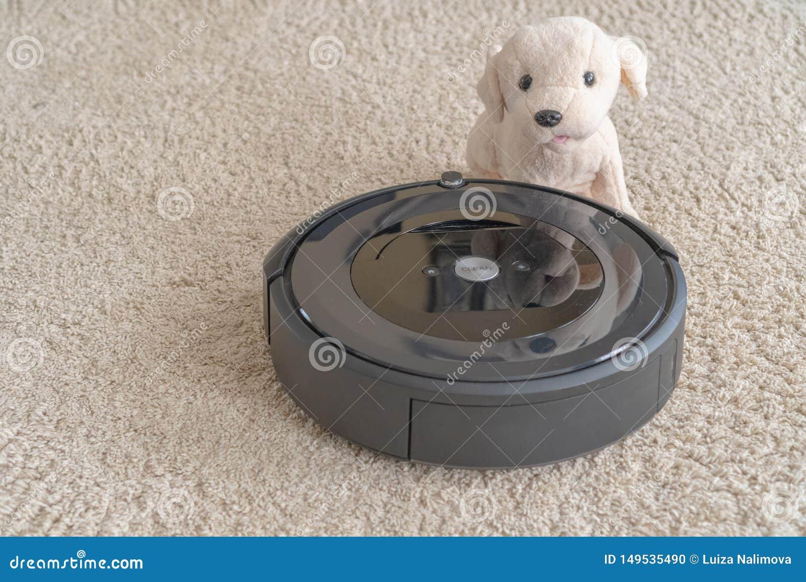 Aspirateur de robot avec un chien sur un tapis beige propre Le concept de la propret? et du confort ? la maison