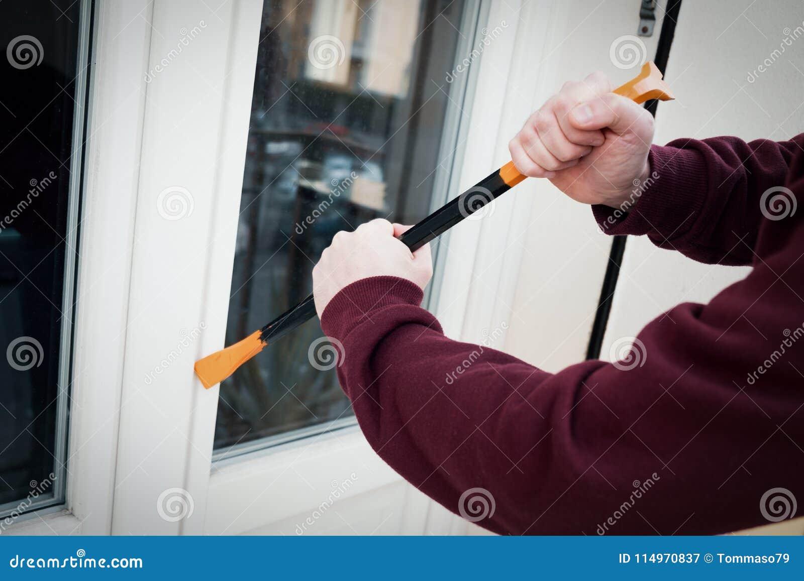 Assaltante encapuçado que força o fechamento de janela para fazer um roubo em uma casa