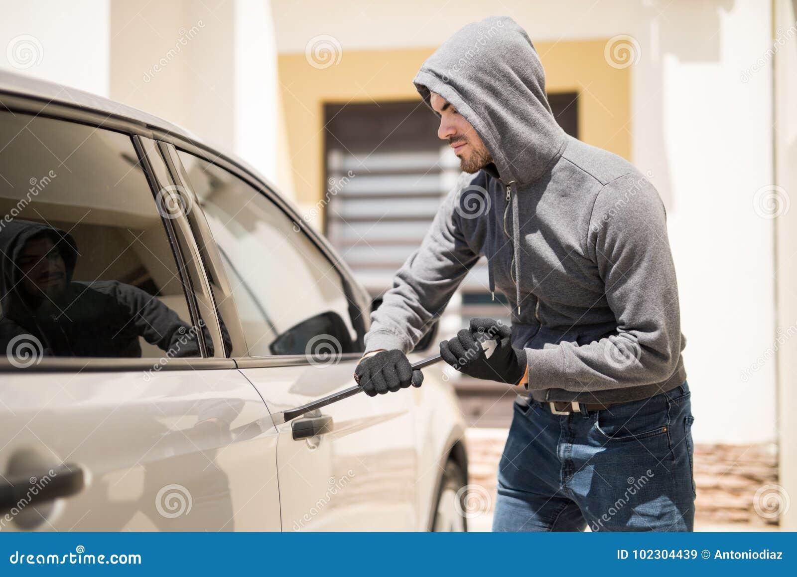 Assaltante que força uma porta de carro