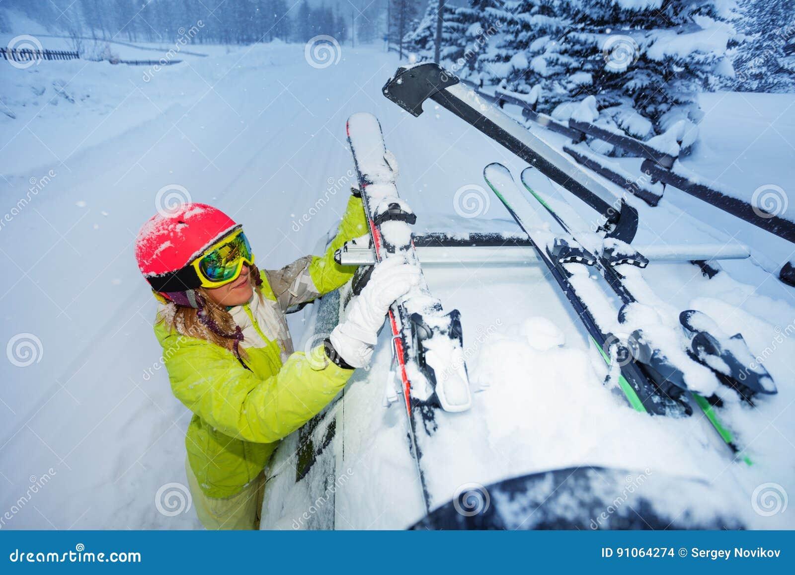 A asseguração fêmea do esquiador esquia aos trilhos do ` s do telhado do carro