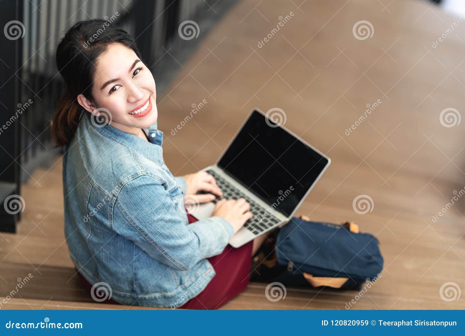 Assento asiático da mulher do retrato, usando o portátil, sorrindo e olhando a câmera