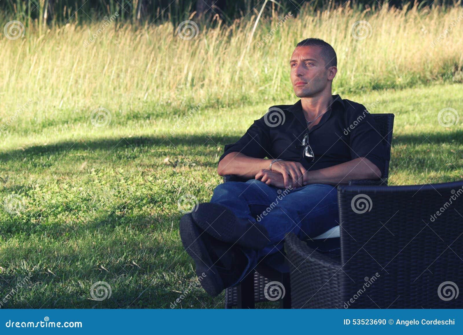 Assento de relaxamento do homem na natureza Conceito do abrandamento