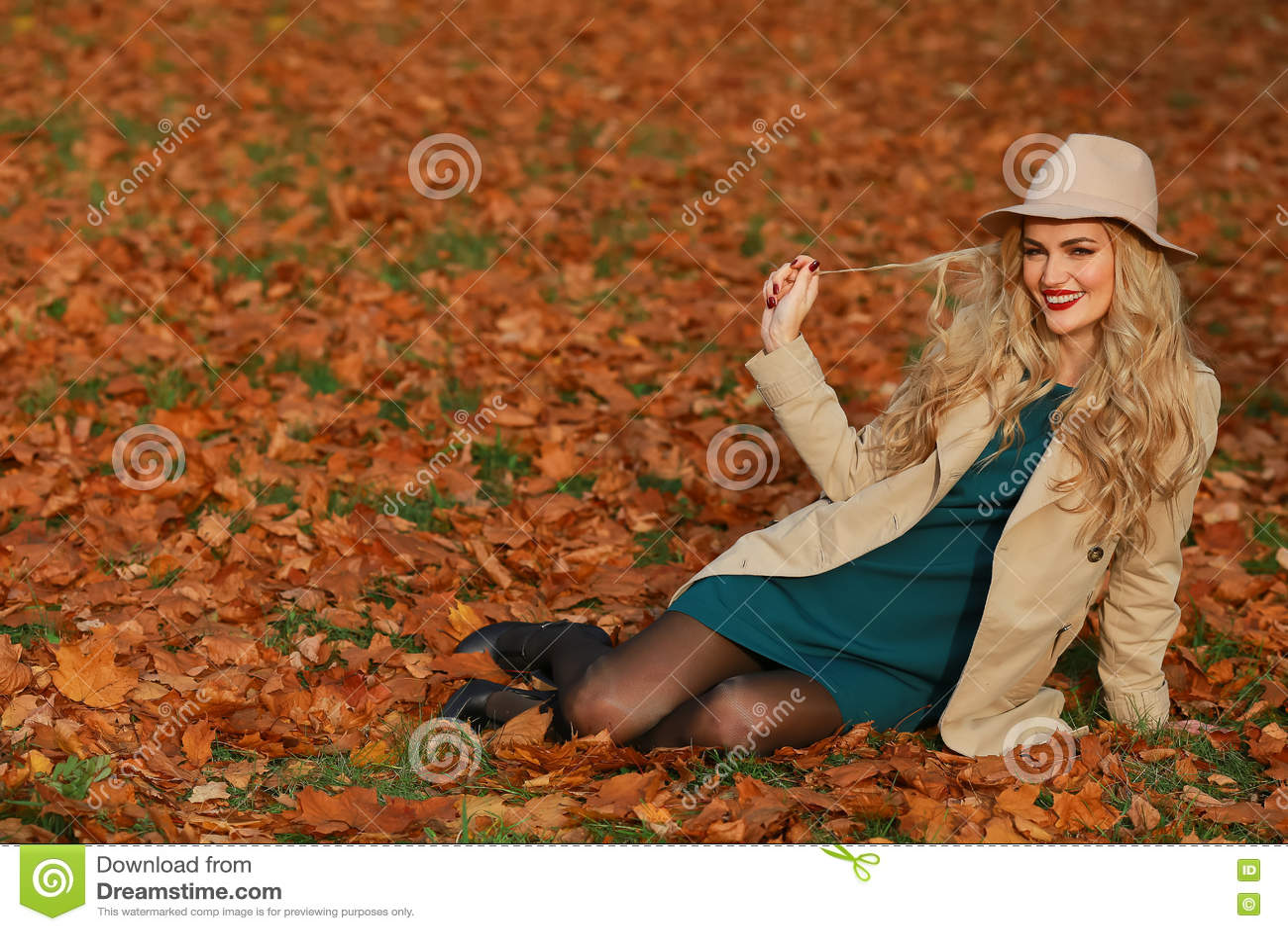 Assento de sorriso da jovem mulher na grama no outono fundo amarelo do jardim do bordo da queda Menina bonita no revestimento e n
