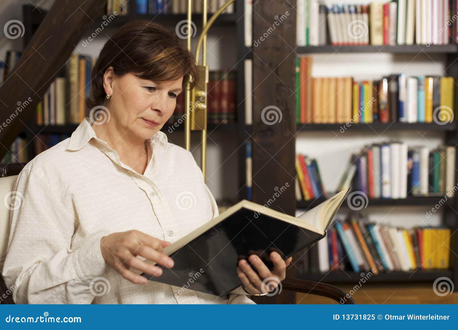 Assento e leitura sênior atrativos da mulher um livro
