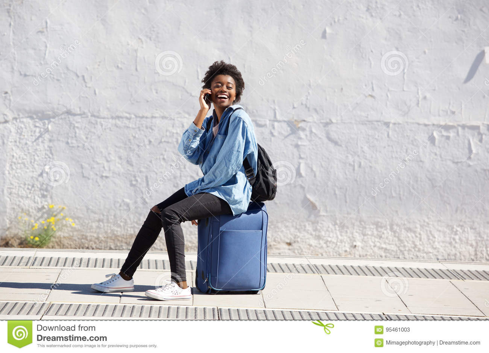 Assento fêmea afro-americano na mala de viagem fora e falando no telefone celular