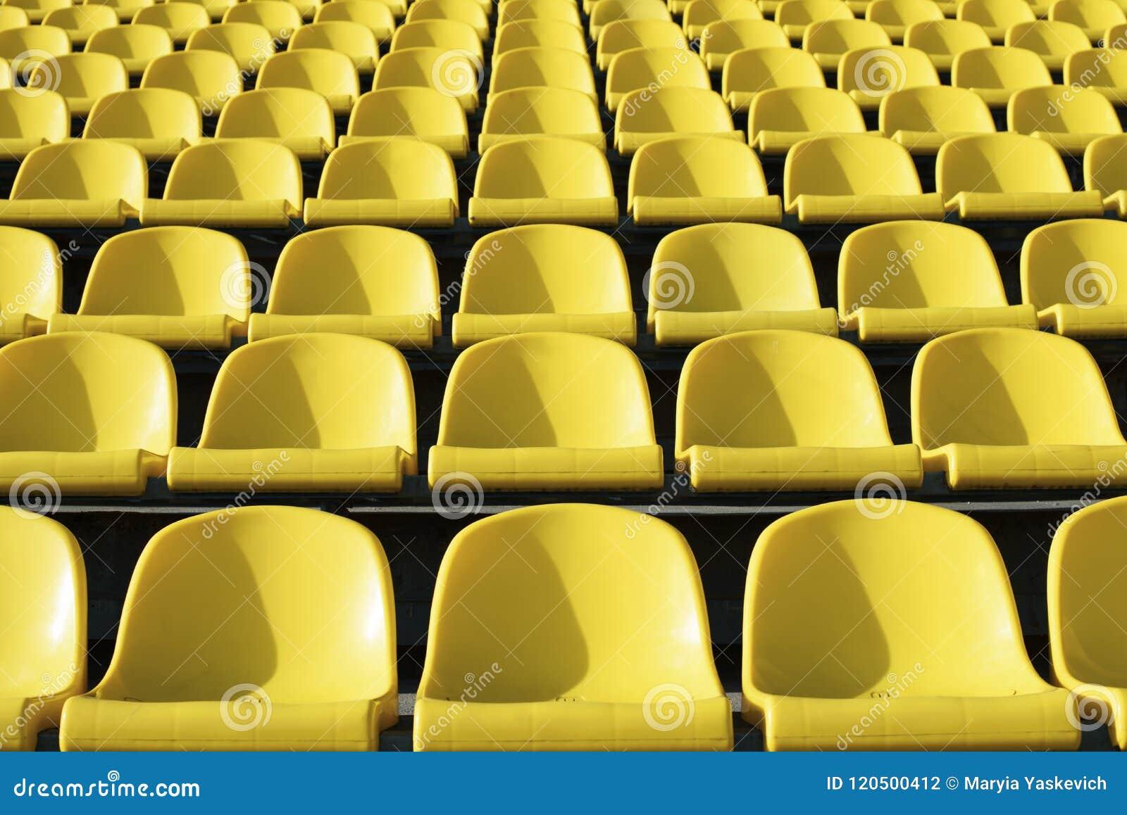Assentos amarelos plásticos vazios no estádio, arena esportiva do estar aberto