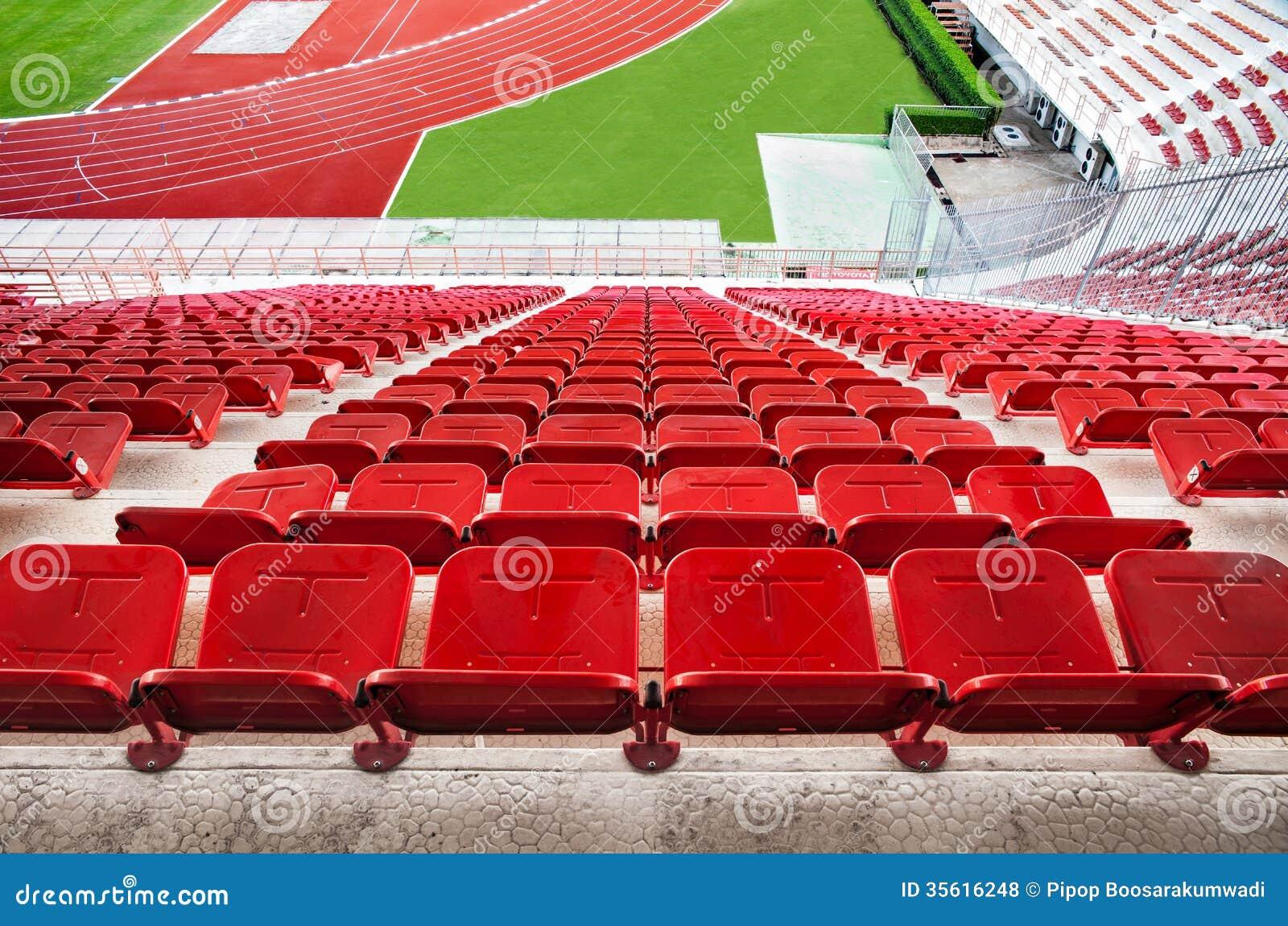 Assentos vermelhos do estádio com pista de atletismo vermelha e grama verde.