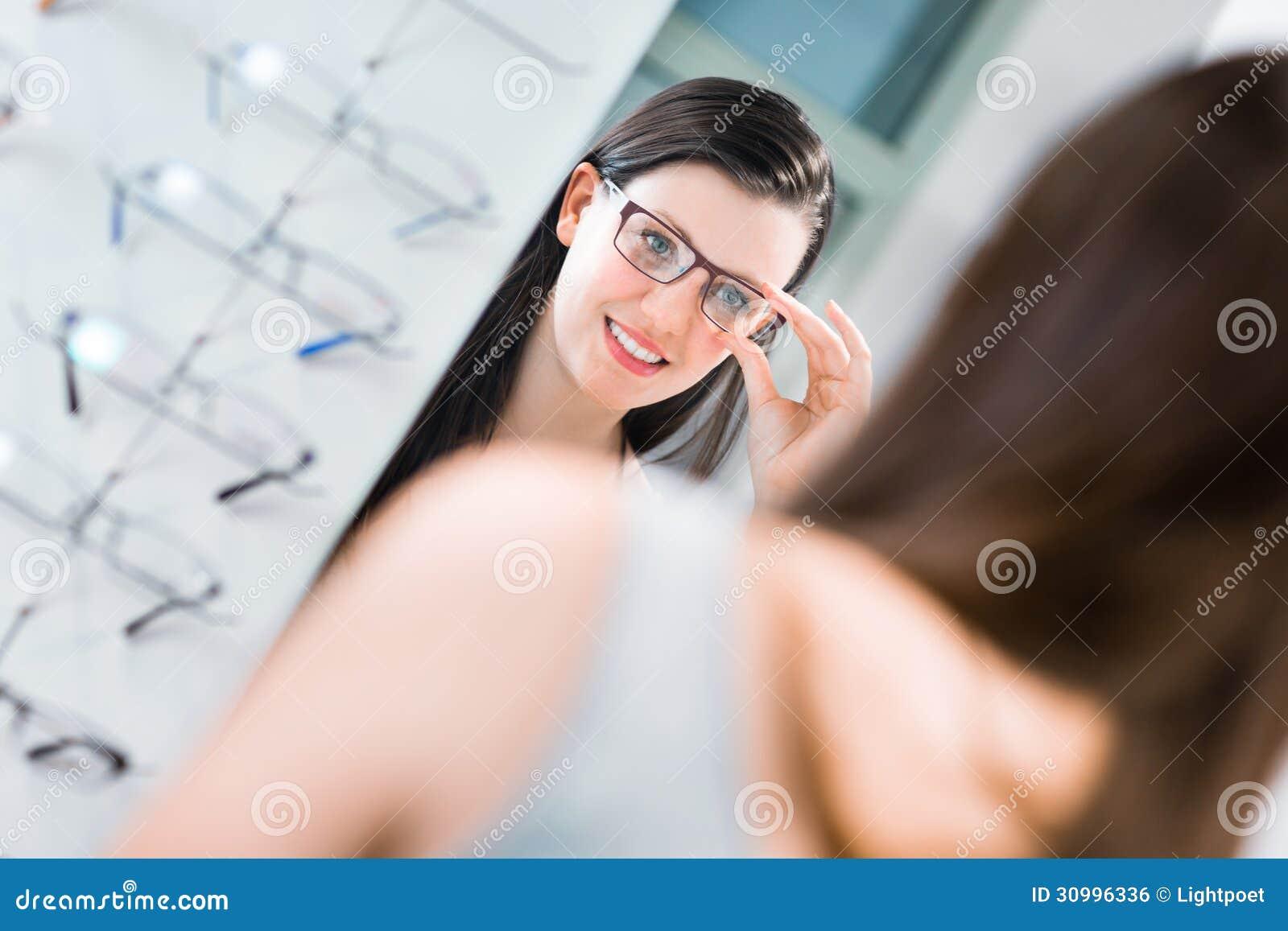 Assez, jeune femme choisissant de nouveaux cadres en verre