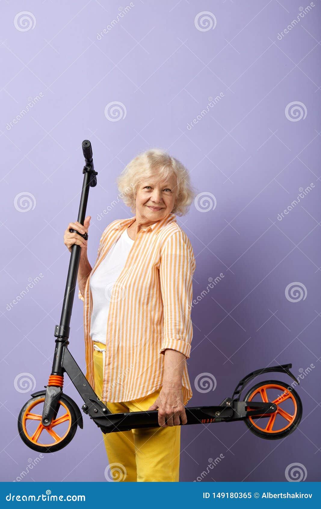 Assim divertimento A mulher idosa feliz mant?m-se no  trotinette  das m?os pronto para um passeio