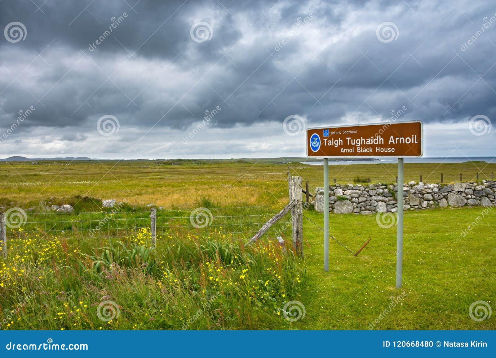 Assine para a casa do preto de Arnol no gaélico com paisagem escocesa bonita no fundo