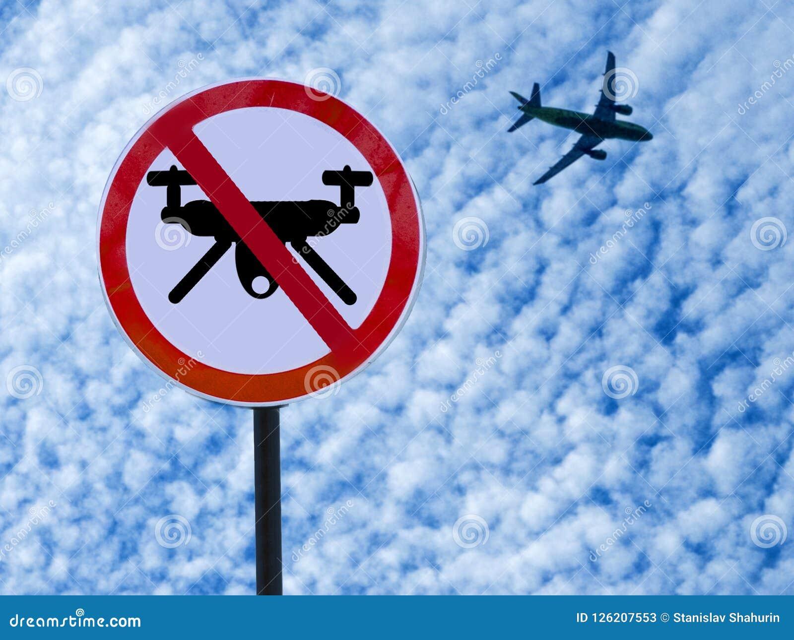 Assine zangões da proibição no fundo do céu com nuvens e plano da descolagem