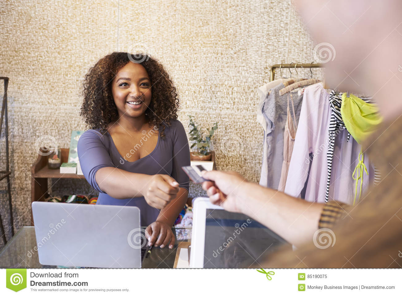 assistant at clothes shop taking credit card from customer stock assistant at clothes shop taking credit card from customer
