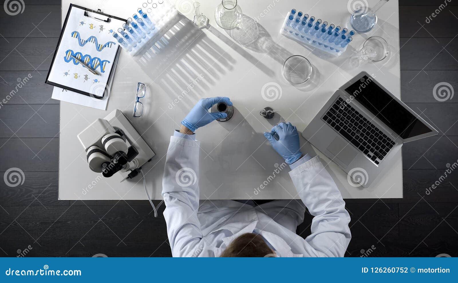 Assistant de laboratoire vérifiant le produit pétrolier dans le flacon, faisant le mélange chimique, vue supérieure