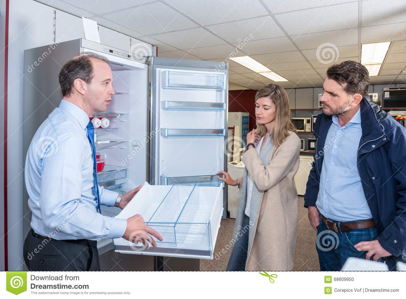 Assistant Demonstrates Refrigerator To Young Couple