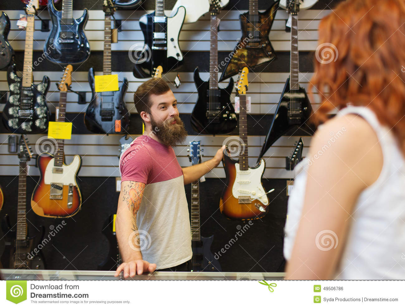 assistant or customer beard at music store stock photo assistant showing customer guitar at music store royalty stock image