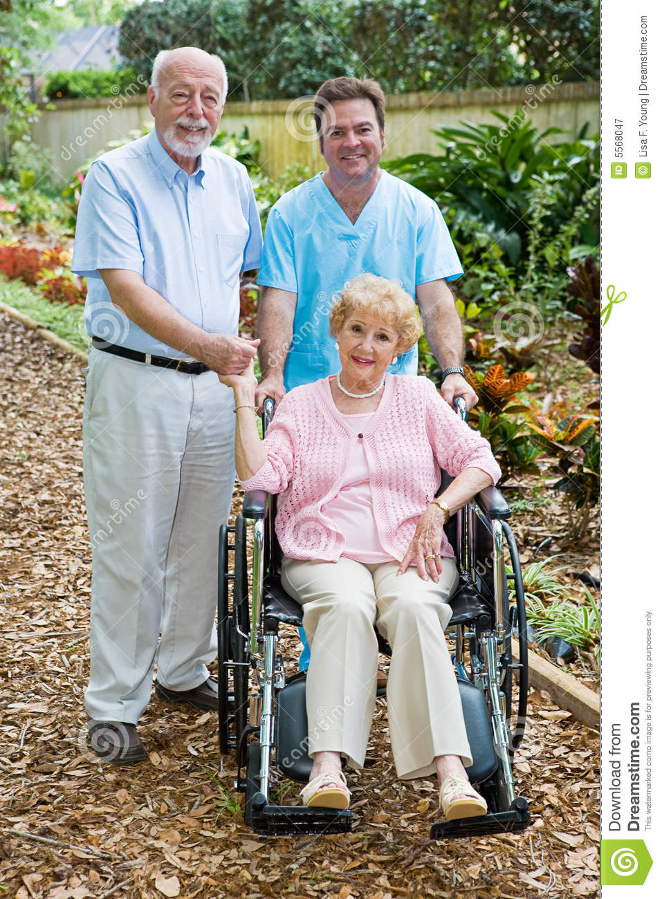 Disabled senior woman and her husband with a male nurse on the grounds ...