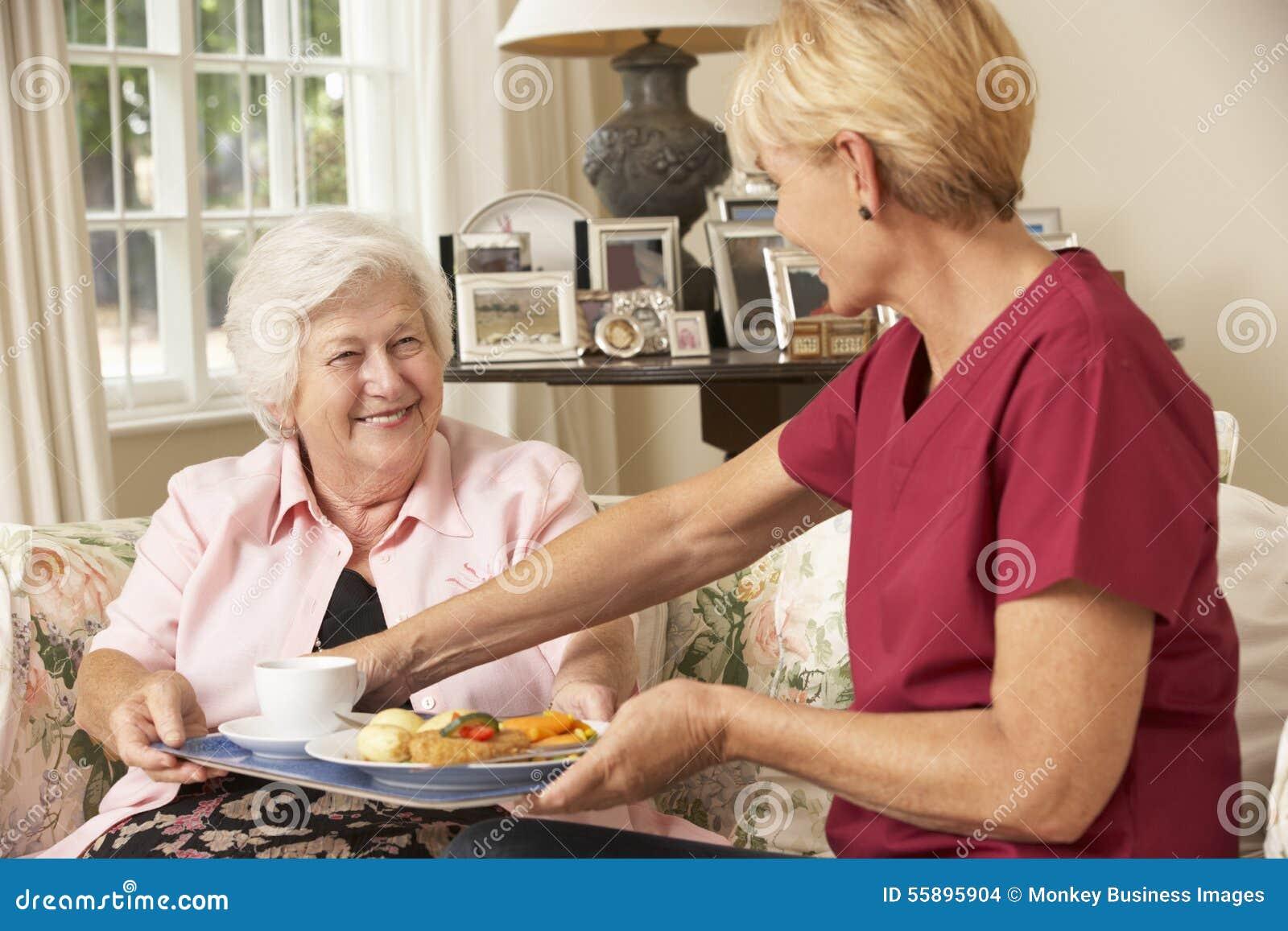 Assistente che serve donna senior con il pasto nella casa di cura