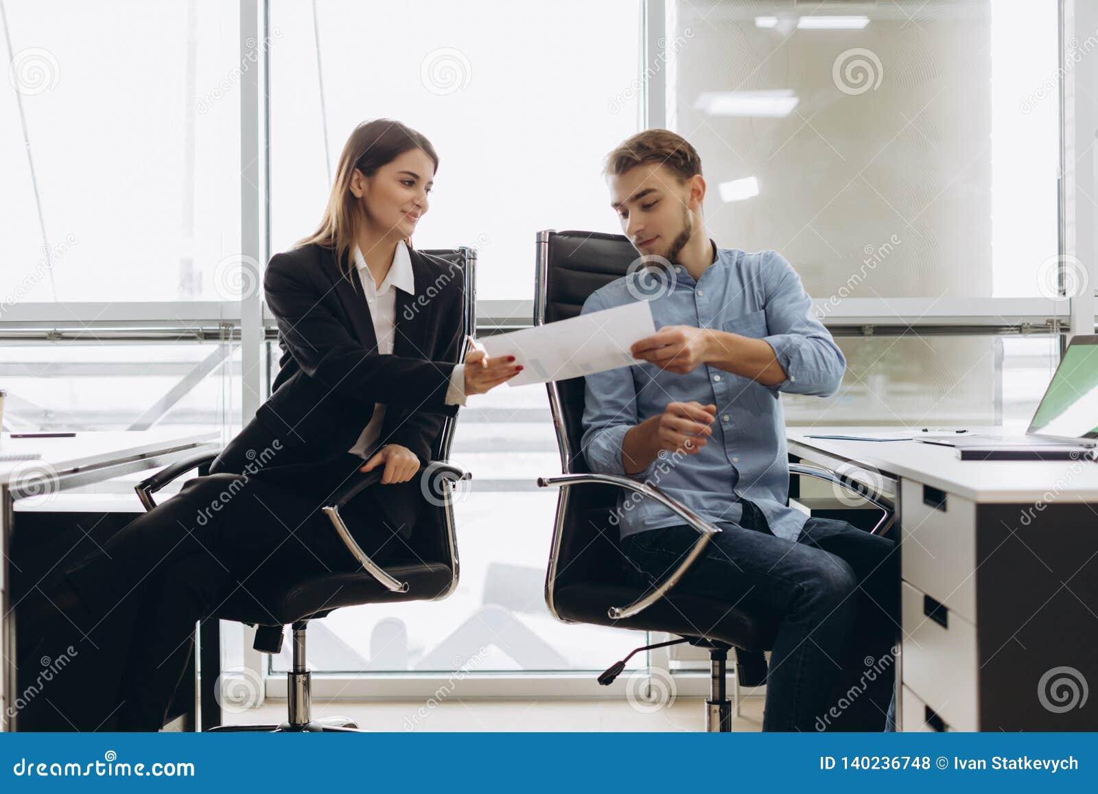 Assistente pessoal de sorriso novo que dá o documento ao trabalhador de escritório em seu escritório, contador fêmea que relata o