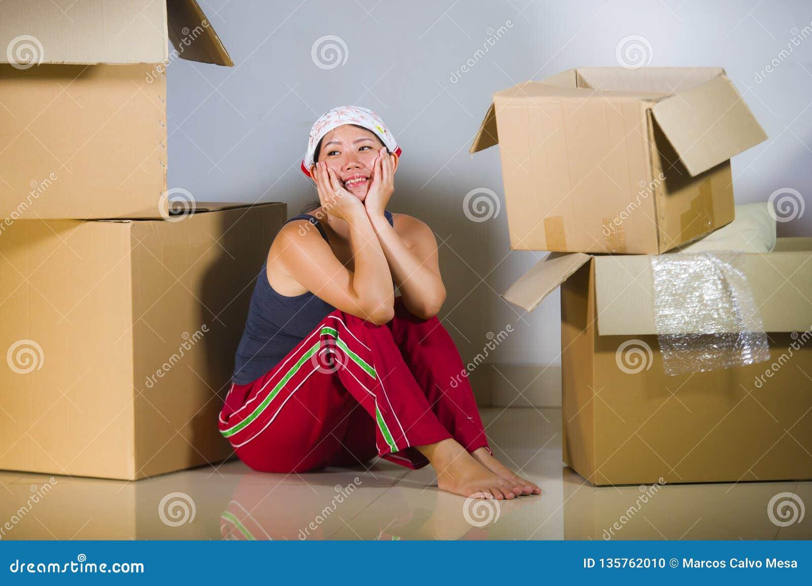 Assoalho entusiasmado novo da sala de visitas da mulher coreana asiática bonita e feliz em casa que desembala pertences das caixa