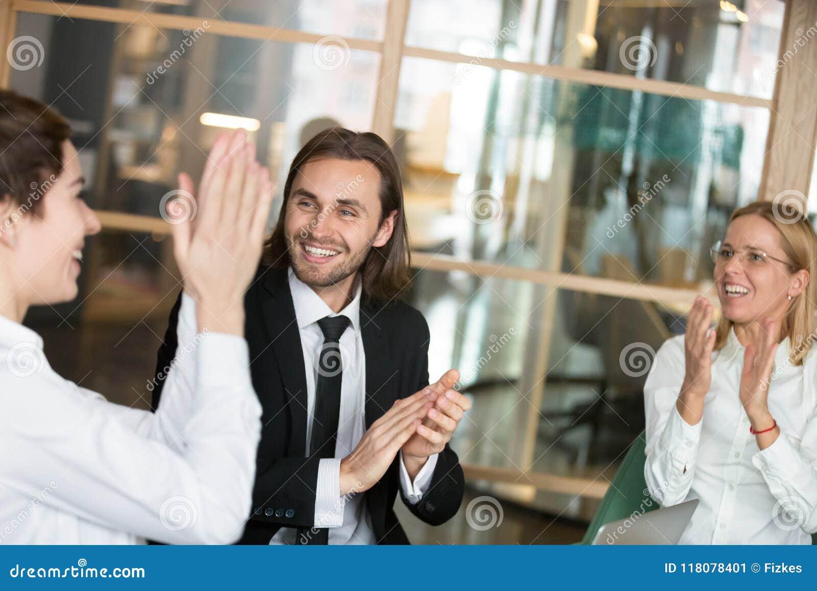 Associés enthousiastes applaudissant félicitant des WI de collègue
