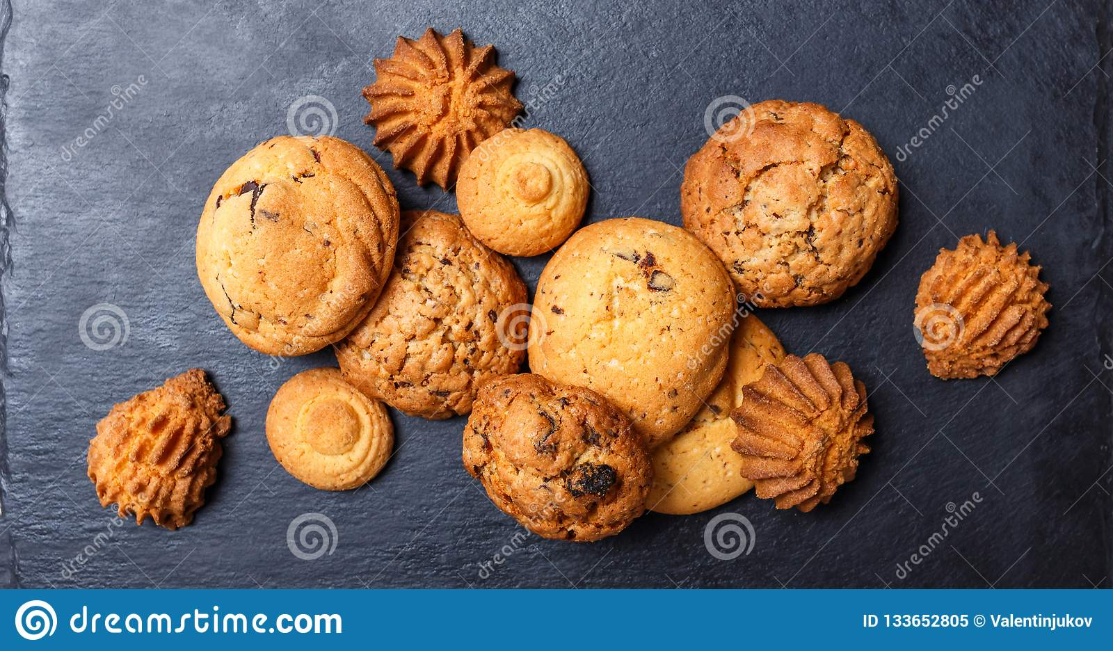 Assorted cookies with chocolate chip, oatmeal raisin on stone slate background on wooden background close up. Homemade baking.