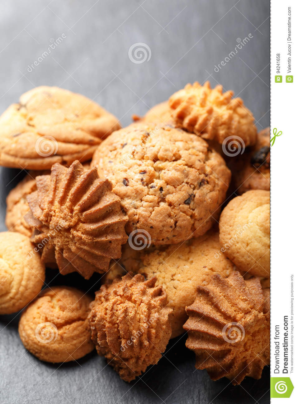 Assorted cookies with chocolate chip, oatmeal raisin on stone slate background on wooden background close up. Homemade baking