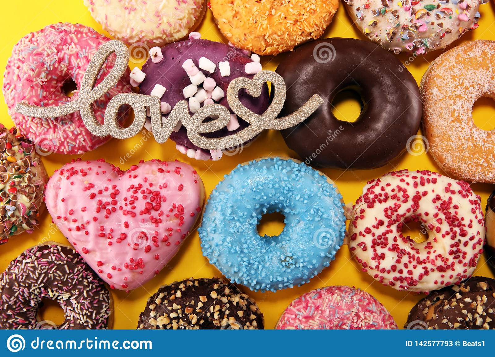 Assorted donuts with chocolate frosted, pink glazed and sprinkles donuts