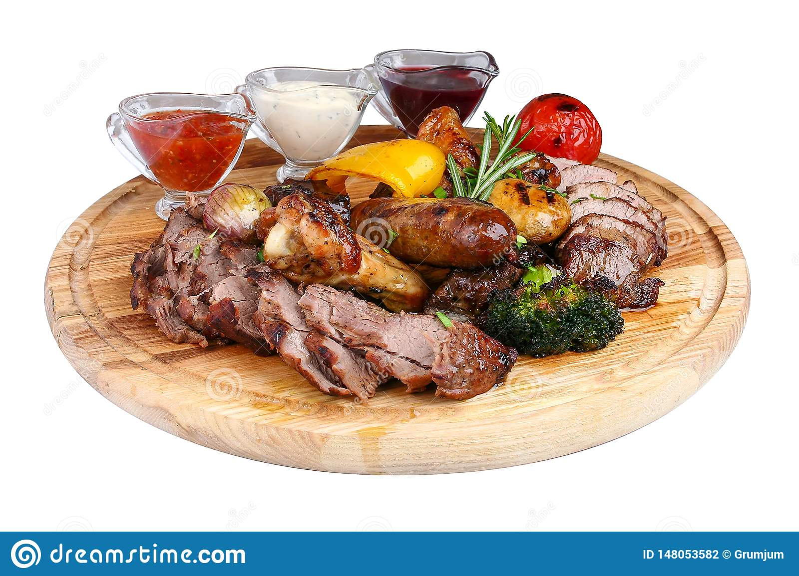 Assorted grilled meat with baked vegetables on a wooden board